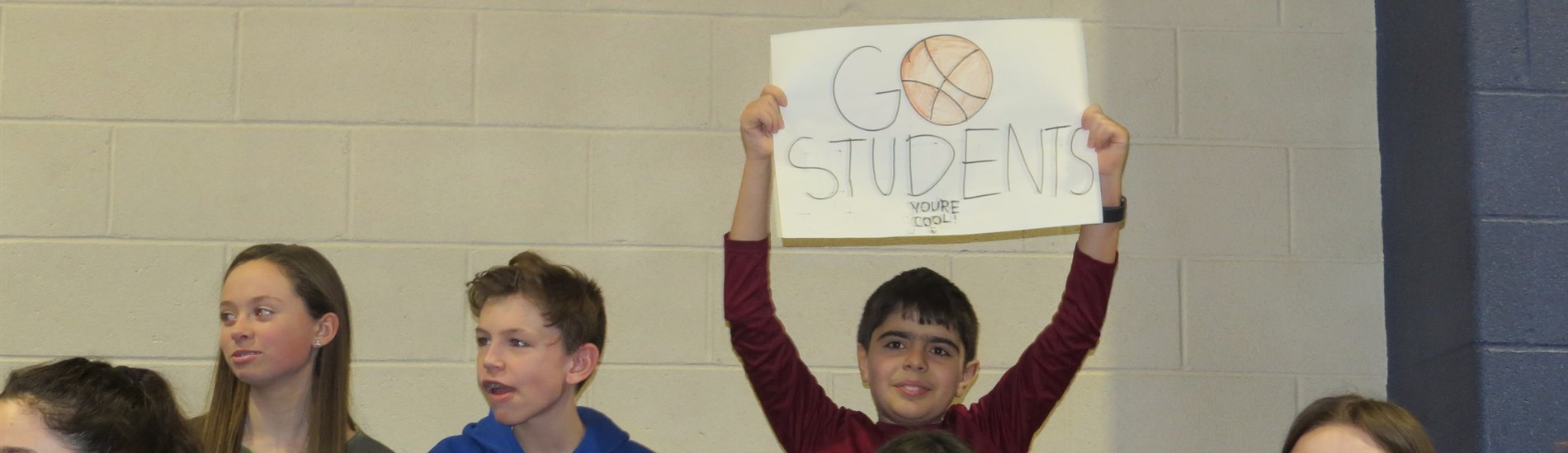 student cheering on the team with a sign
